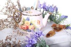 Porslinkokkärlet med te och lilan blommar på en vit tabell Arkivfoton