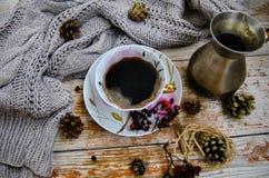 Porslinkopp av svart kaffe och kaffekannan på den lantliga bakgrunden med vintergarnering Arkivfoto