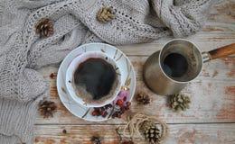 Porslinkopp av svart kaffe och kaffekannan på den lantliga bakgrunden med vintergarnering Fotografering för Bildbyråer