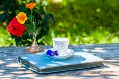 Porslinkopp te och den härliga våren blommar i vas på en trätabell i trädgården Sommarparti Royaltyfri Bild