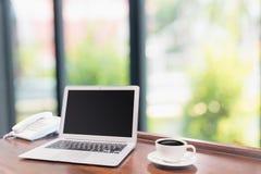 Portáteis com a caneca de café branco na mesa de madeira Imagens de Stock Royalty Free
