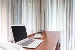 Portáteis com a caneca de café branco na mesa de madeira Foto de Stock Royalty Free