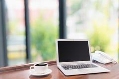 Portáteis com a caneca de café branco na mesa de madeira Fotografia de Stock Royalty Free