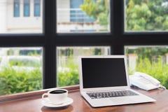 Portáteis com a caneca de café branco na mesa de madeira Imagens de Stock