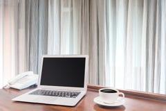 Portáteis com a caneca de café branco na mesa de madeira Imagem de Stock