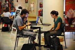 Portáteis do uso dos povos em um café Fotografia de Stock Royalty Free