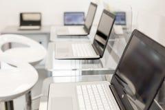 Portáteis novos, abertos, em um desktop de vidro; cadeiras brancas modernas no fundo Foto de Stock Royalty Free