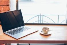 Portátil aberto e uma xícara de café na tabela no café, conceito autônomo imagem de stock