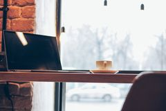 Portátil aberto e uma xícara de café na tabela no café, conceito autônomo foto de stock