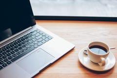 Portátil aberto e uma xícara de café na tabela no café, conceito autônomo fotografia de stock