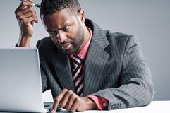 Portátil afro-americano novo de Being Sneaky On do homem de negócios foto de stock royalty free