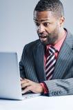 Portátil afro-americano novo de Being Sneaky On do homem de negócios Foto de Stock