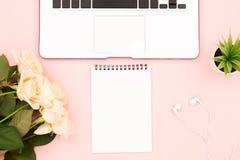 Portátil, artigos de papelaria e rosas fotografia de stock royalty free