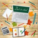 Portátil com de volta a mensagem da escola, calculadora, folhas de outono e fontes de escola no fundo de madeira - vista superior Fotografia de Stock