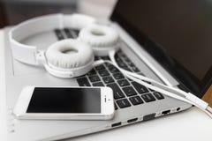 Portátil com fones de ouvido e close-up do telefone celular Fotografia de Stock