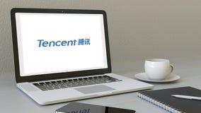 Portátil com logotipo de Tencent na tela Rendição conceptual do editorial 3D do local de trabalho moderno Foto de Stock Royalty Free