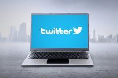Portátil com logotipo do gorjeio na tela Imagens de Stock