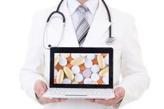 Portátil com os comprimidos nas mãos do doutor isoladas no branco imagens de stock royalty free