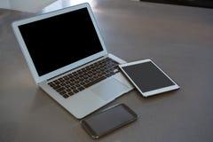 Portátil com tabuleta e telefone no contador de cozinha Fotos de Stock Royalty Free