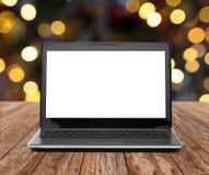 Portátil com a tela branca sobre luzes de Natal Foto de Stock