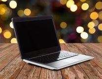Portátil com a tela preta sobre luzes de Natal Imagens de Stock Royalty Free