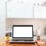 Portátil com a tela vazia sobre a tabela de madeira dentro Fotografia de Stock Royalty Free