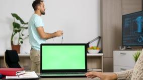 Portátil com a tela verde na tabela na sala de visitas filme
