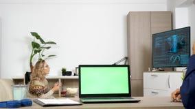 Portátil com uma tela verde na tabela na sala de visitas video estoque