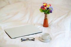 Portátil com vidros e copo de café no fundo branco imagens de stock