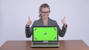 Portátil da exibição da mulher de negócios e da doação polegares louros felizes novos acima na mesa vídeos de arquivo