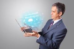 Portátil da terra arrendada do homem com conceito de sistema baseado nuvem fotografia de stock