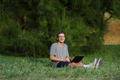 Portátil da terra arrendada do menino e câmera alegres novos rir ao sentar-se no parque da grama em público Estudante que tem o b fotografia de stock