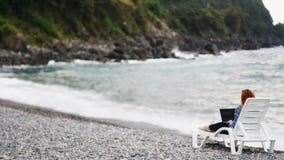 Portátil da terra arrendada da jovem mulher nos joelhos que relaxam perto do mar filme