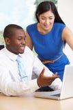 Portátil de And Businesswoman Using do homem de negócios no escritório imagens de stock royalty free