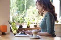 Portátil de datilografia da mulher ao lado da janela Imagens de Stock Royalty Free