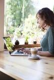 Portátil de datilografia da mulher verde da camisa Foto de Stock