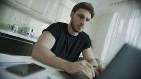 Portátil de datilografia do homem sério em casa Homem de negócio que usa o computador na cozinha video estoque