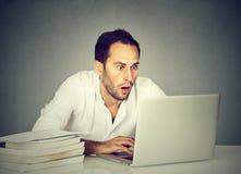Portátil de observação chocado do homem ao estudar fotos de stock