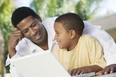 Portátil de And Son Using do pai junto Imagens de Stock Royalty Free