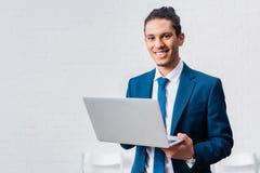 Portátil de sorriso da terra arrendada do homem de negócios no branco fotos de stock royalty free