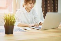 Portátil de trabalho da mão da mulher de negócio na mesa de madeira no escritório na luz da manhã imagem de stock