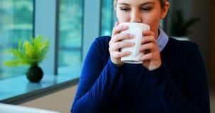 Portátil de utilização executivo fêmea ao comer o café video estoque