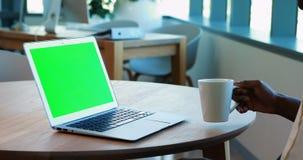Portátil de utilização executivo fêmea ao comer o café vídeos de arquivo