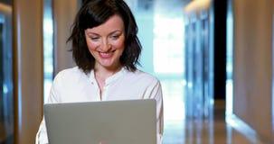 Portátil de utilização executivo fêmea no corredor video estoque