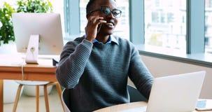 Portátil de utilização executivo masculino ao falar no telefone celular vídeos de arquivo