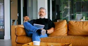Portátil de utilização executivo no sofá no escritório 4k filme