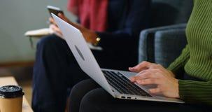 Portátil de utilização executivo no sofá no escritório 4k video estoque