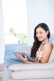 Portátil de vista moreno bonito da câmera e da utilização no sofá foto de stock royalty free