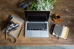 Portátil, diários, câmera da foto do vintage e xícara de café no tabletop de madeira Fotos de Stock Royalty Free