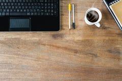 Portátil do computador, cadernos, copo de café e penas na tabela de madeira do vintage do grunge Imagem de Stock